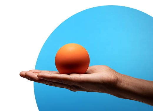 Person holding an orange in front of a blue background